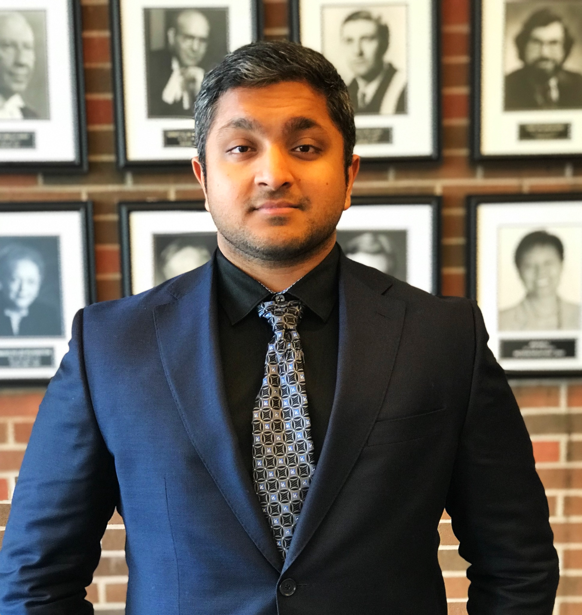 Photo of Program Coordinator Christopher Dias, in front of the Deans' Portraits at Osgoode